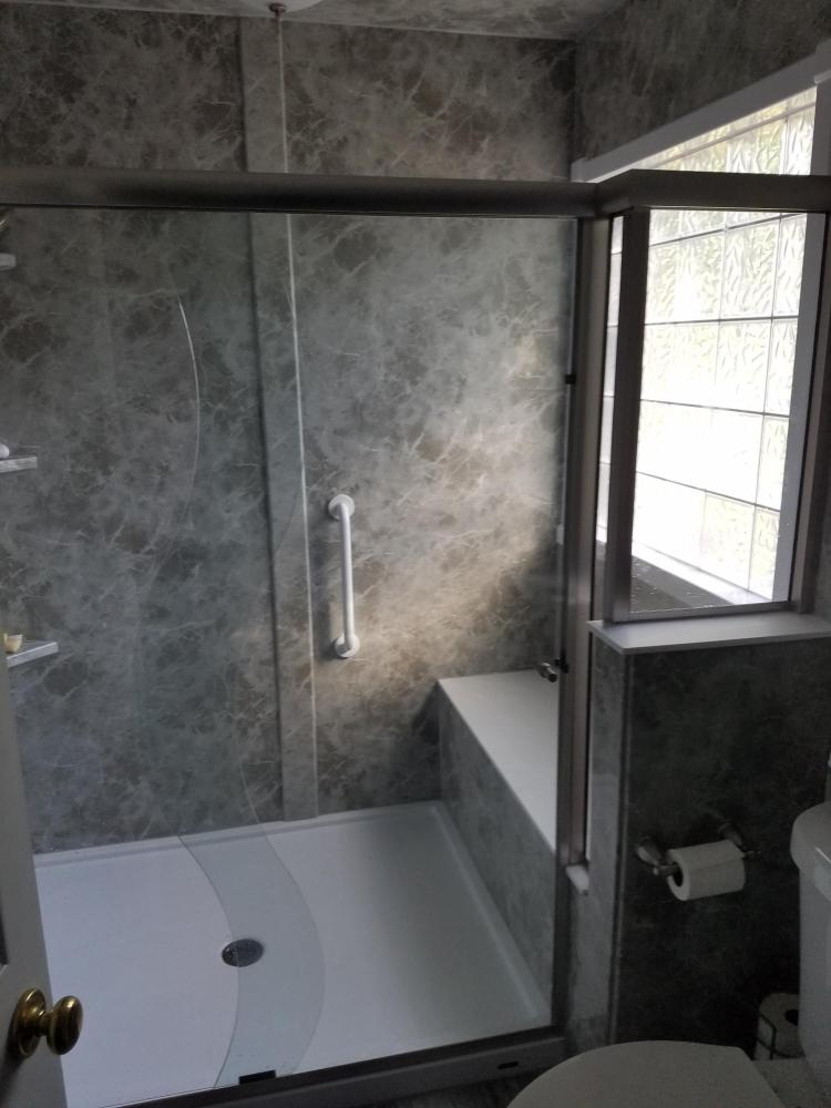 This new shower features a low threshold shower pan, a custom bench and a semi frameless shower door.  This large, walk in shower has Moen fixtures including a hand-held shower sprayer. Installed near Columbus, GA.