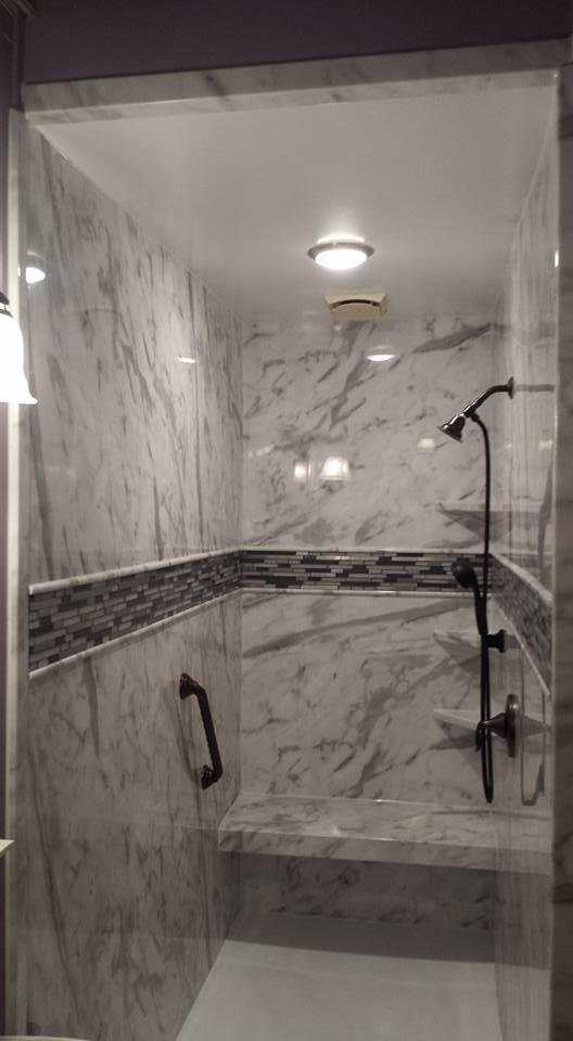A newly remodeled shower in White Calcutta with decorative tile band