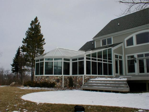 A beautiful sunroom shown in white with glass cathedral roof