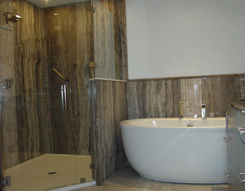 Master Bathroom Remodel Featuring ReBath's Silver Travertine Natural Stone Walls and a Freestanding Soaking Tub.