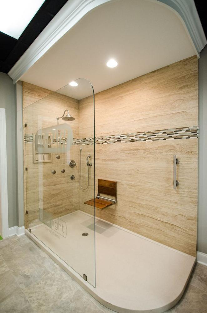 Travertine Stone Shower with decorative grab bars and folding teak bench by Moen.