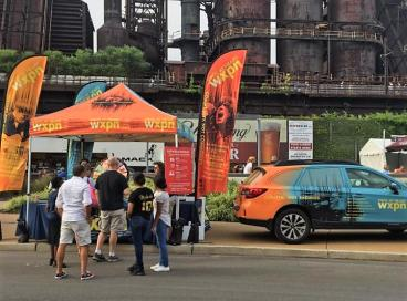 WXPN Vehicle Wrap, Tent, and Flags at 2017 Music Fest in front of Bethlehem Steel