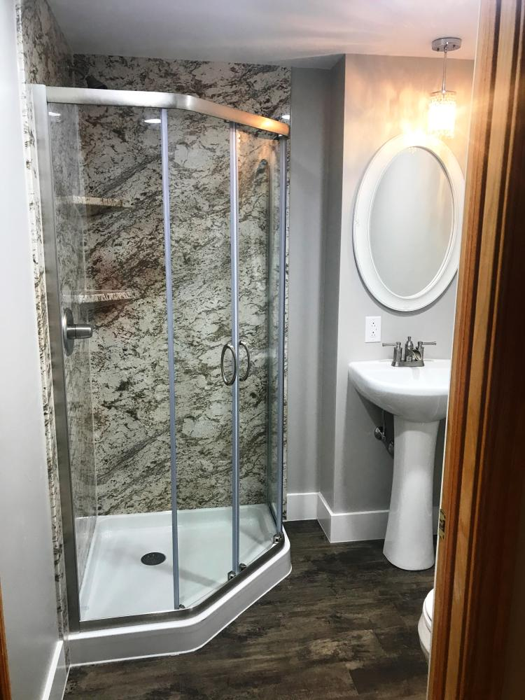 Beautiful Rebath Biscayne wall system, complemented with vinyl plank flooring, is the highlight of this remodel.  Clear glass doors and pedestal sink give this room a more spacious feeling.