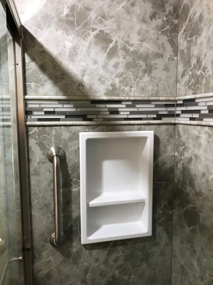 A walk-in shower in Gray Emperador Durabath SSP with a shower nice and safety grab bar in brushed nickel give support and accessibility to this new shower.