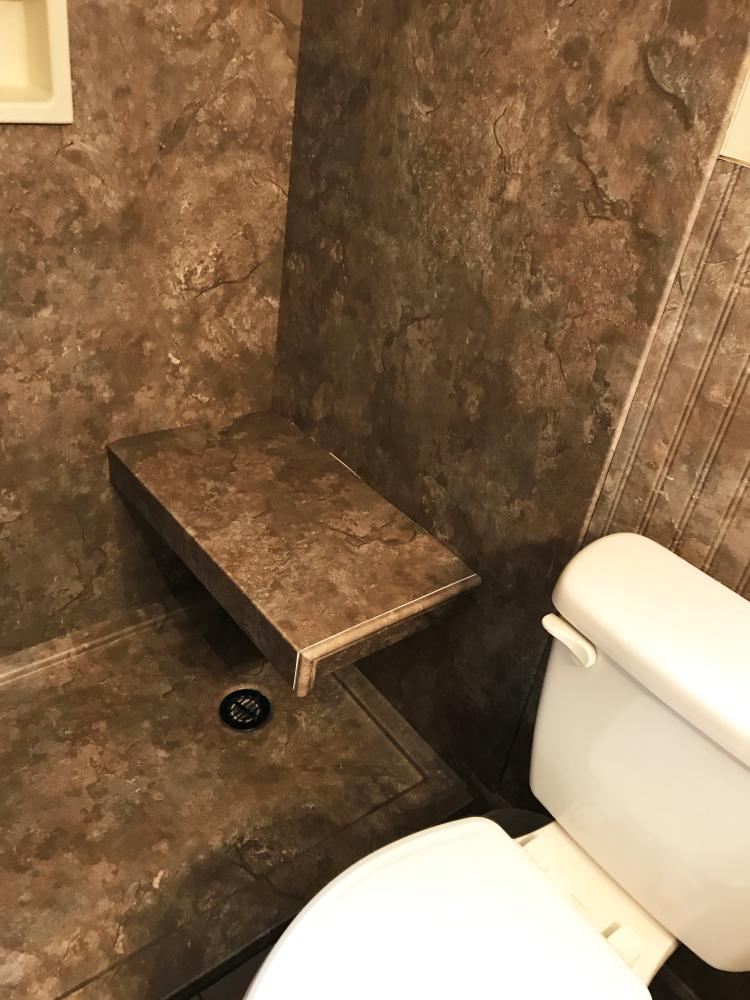 This accessible shower remodel features a wrapped bench seat and custom shower pan in Desert Stone Durabath SSP to match the walls.