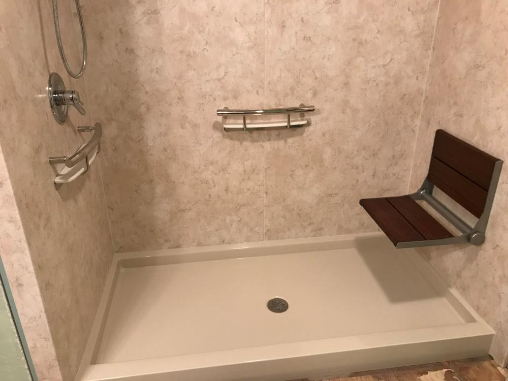 Rebath Tivoli Travertine walls complimented with an Invisia seat and shampoo shelf provide an open feeling.