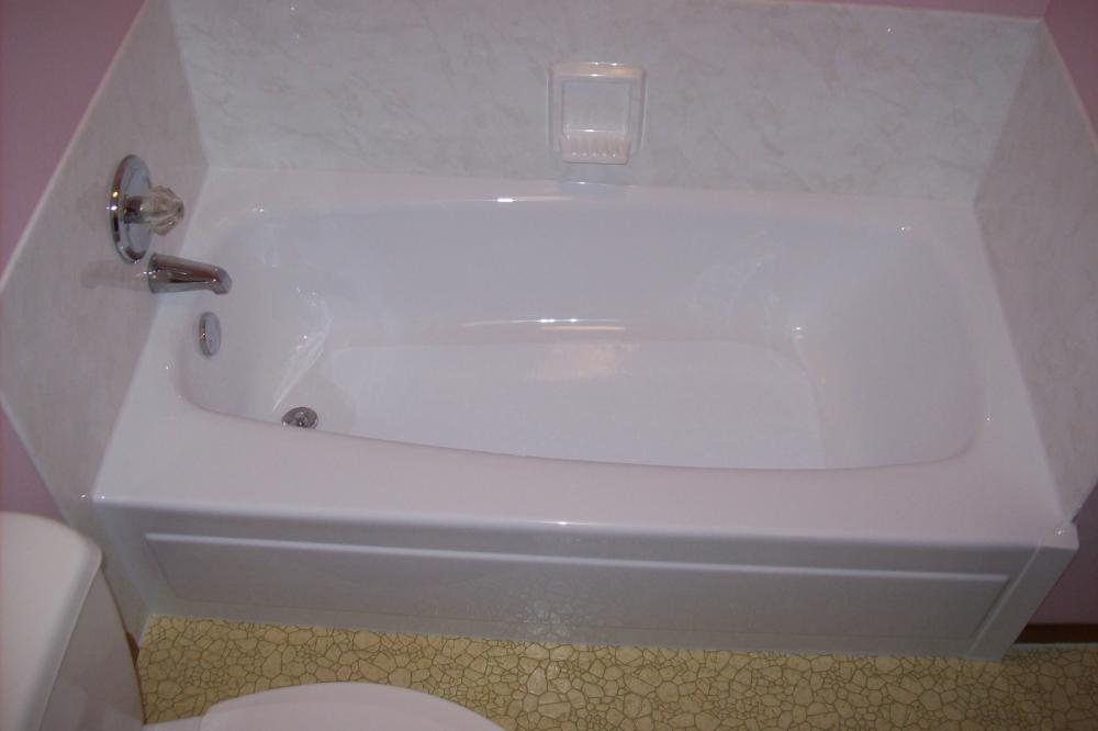 We install a white tub liner over the green tub and a white marble colored wall surround with traditional soap dish