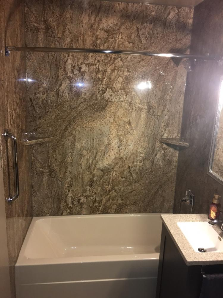 We removed the old fiberglass tub and tub surround.  Installed biscuit tub and Tahoe Granite wall surround with corner shelves and grab bars