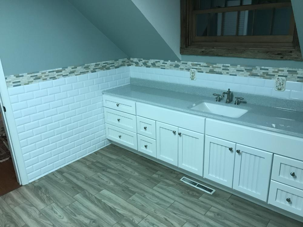 White classic subway wainscot with the decorative mosaic tiles, white centennial style vanity, lotus onyx vanity top with clean white bowl, and the beautiful and popular naturale floating porcelain tile planks!