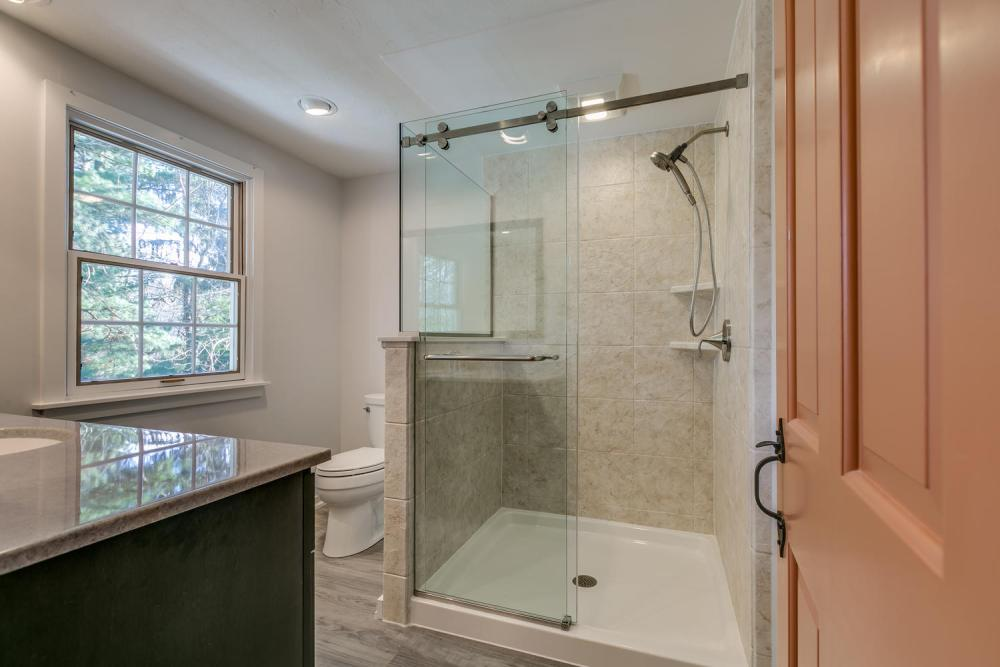 We replaced the old closed in shower and opened up the space to allow more light into the bathroom.  This new, larger shower included a knee wall and customer glass shower door.