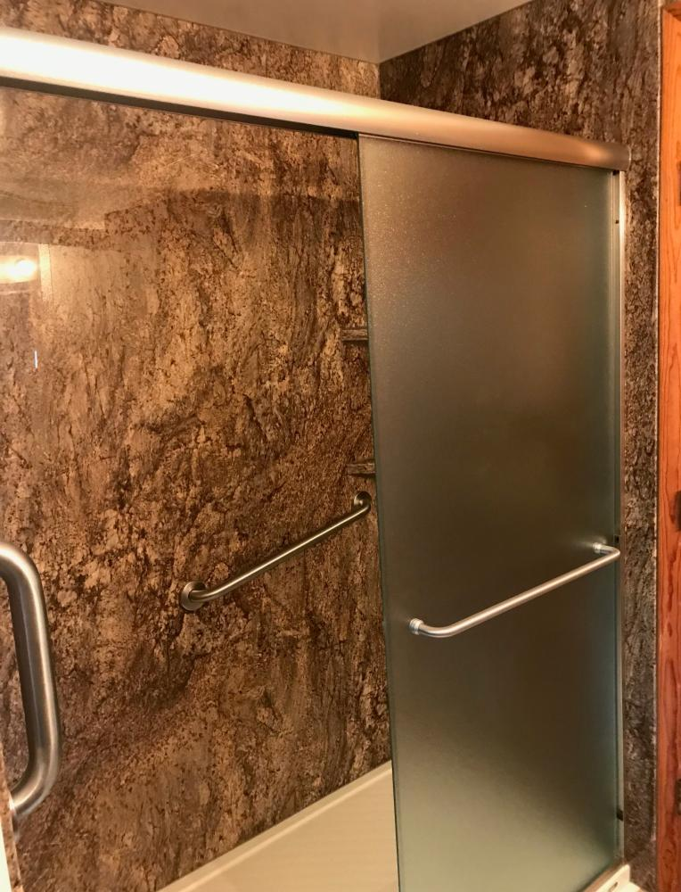 Tahoe Granite wall system with a biscuit shower base and shower doors with obscure glass.