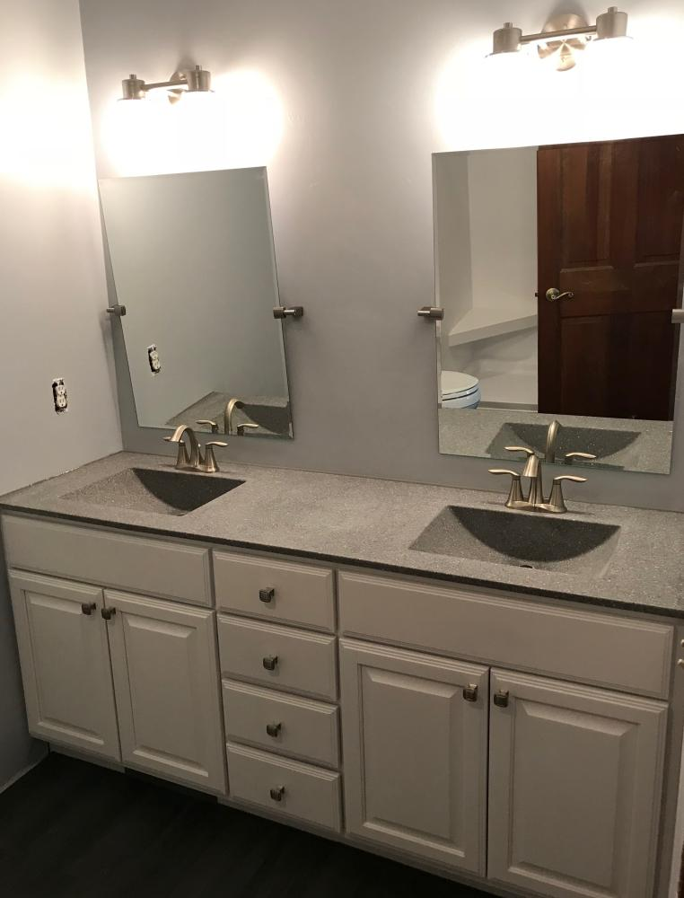 Bertch vanity in white with wave bowls.  Creative Specialties lighting with Gatco mirrors and Moen Eva faucet.  Along with Cerdisa Charcoal porcelain wood tile and black grout.