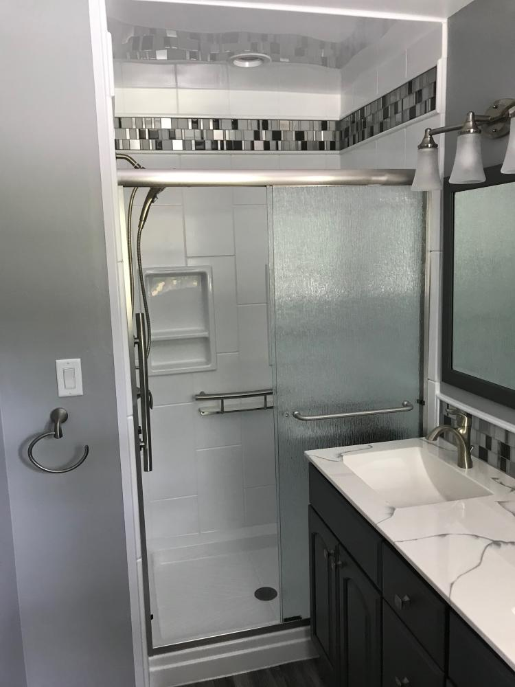 White DuraBath SSP base with white DuraBath walls and mosaic white/charcoal/grey stainless steel inlay. Rain shower door, Invisia shampoo shelf, Invisia accent bar.
