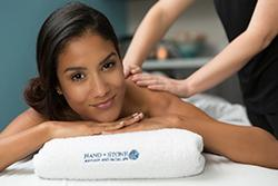Woman with tan skin and dark hair laying down receiving Swedish massage therapy