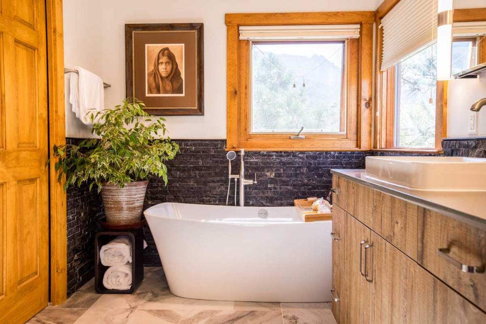 Modern freestanding tub installed with marble flooring and a unique natural stone wainscoting.