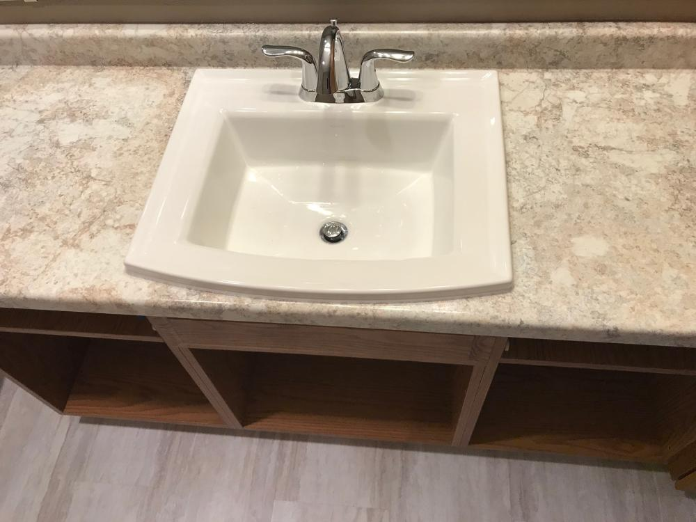 Adura Cascade Seamist luxury vinyl flooring, Kohler Rectangular sink with Formica Vanity top - Crema Mascarello in Radiance finish with backsplash.
