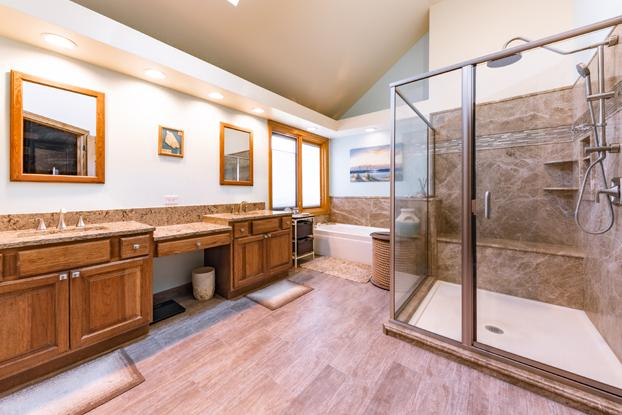 Natural stone in light emperador walk-in shower. DuraCeramic flooring in Mind Swept.