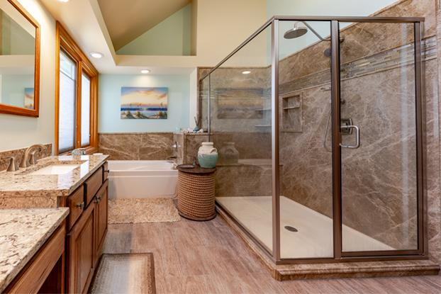 Light Emperador natural stone with a tile accent in the shower. Brushed nickel Moen fixtures with updated oak custom cabinets and solid surface counter tops.