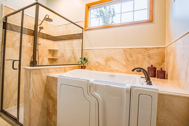 Natural stone shower and tub surround in French Mocha with Oil Rubbed Bronze Moen Fixtures.
