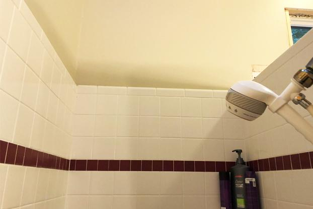 Plastic hand-held shower head. Out-dated tile design and issues with grout in shower.