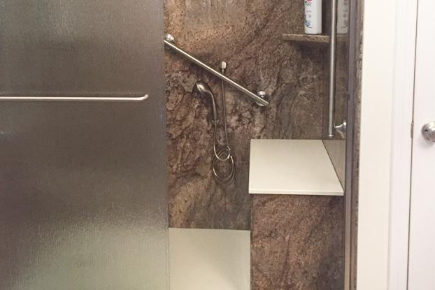 This solid surface polymer shower in Tahoe Granite with custom bench, grab bar, non-slip Onyx flooring, and ADA compliant hand-held shower head provides a safe place to shower.