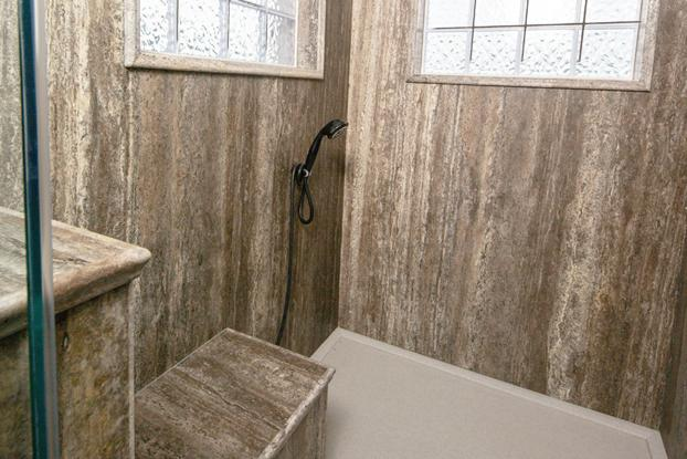Beautiful Natural Stone shower in Silver Vein has a lot of natural light, hand-held shower wand next to a custom bench. This shower also features low-profile entry and non-slip Onyx floors.