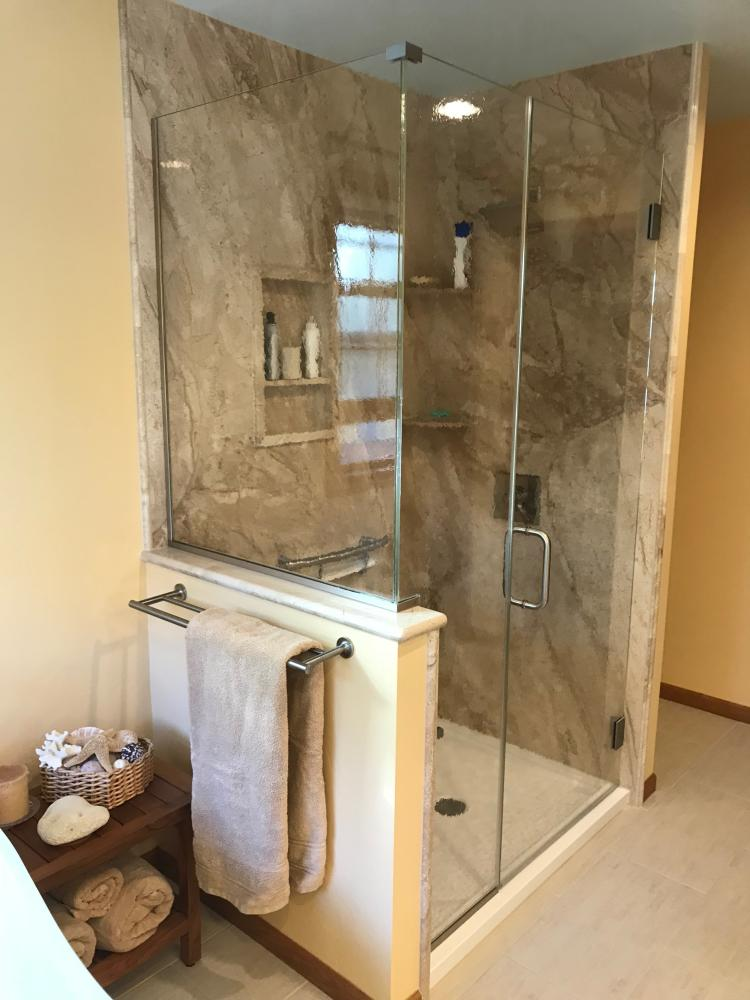 French Mocha Natural Stone wall surround with white Durabath shower base. Invisia fold down seat and shampoo shelf and stainless steel fixtures.