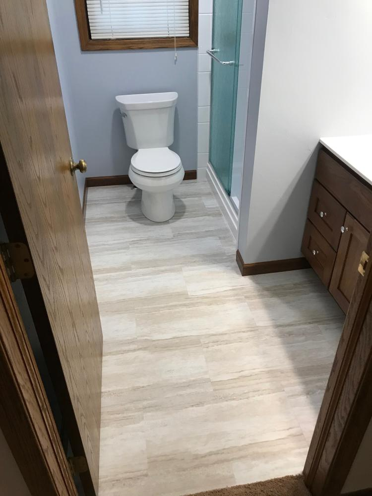 Adura Cascade Sea Mist Luxury Vinyl tile flooring with a new Kohler Wellworth, standard height round white toilet.