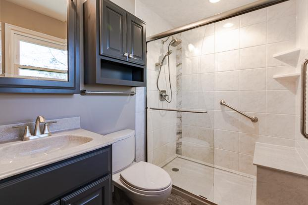 Small bathroom full remodel with a tub to shower conversion that includes aging and accessibility solutions such as grab bars, handheld, and bench seating. The customer also added a taller toilet and more storage.