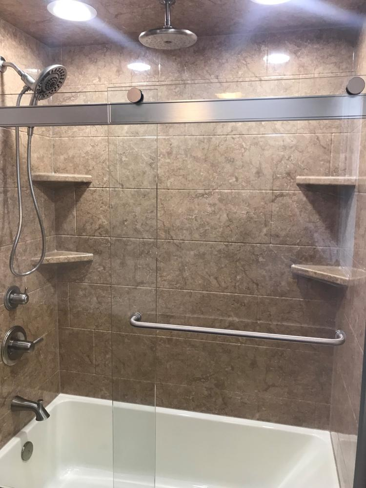 DuraBath SSP Venetian Stone Wall surround in 10 X 20 Horizontal Tile with Gloss finish and a Biscuit base. Corner shelves in Venetian Stone and ceiling mount rain can shower head and in2ition handheld with Brushed Nickel fixtures.