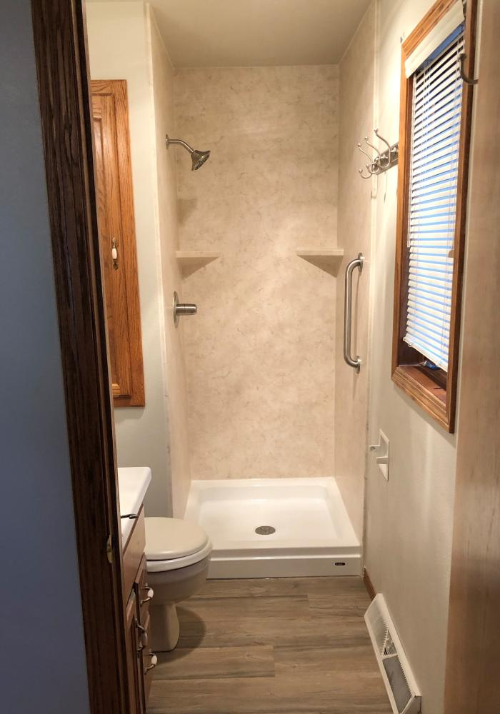 DuraBath SSP Tivoli Travertine walls with a white base and brushed nickel fixtures.