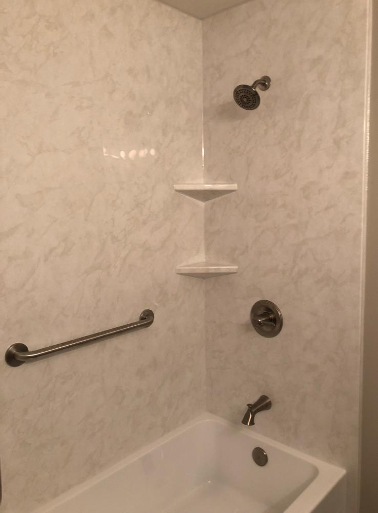 DuraBath SSP White Marble walls and white tub with brushed nickel fixtures.