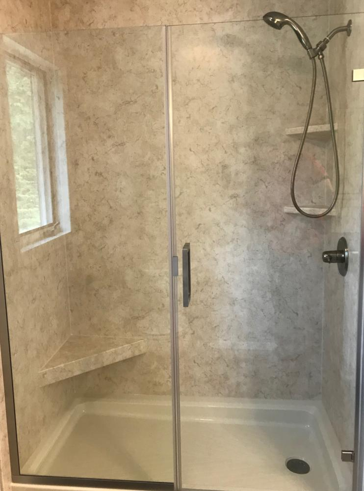 Biscuit standard base with Tivoli Travertine smooth walls in matte finish. Brushed nickle fixtures with clear door.