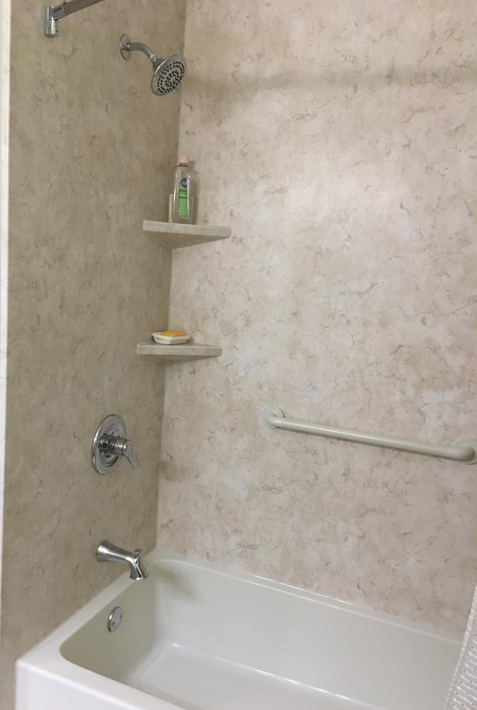 Biscuit tub with SSP Tivoli Travertine walls and shelves in a matte finish.