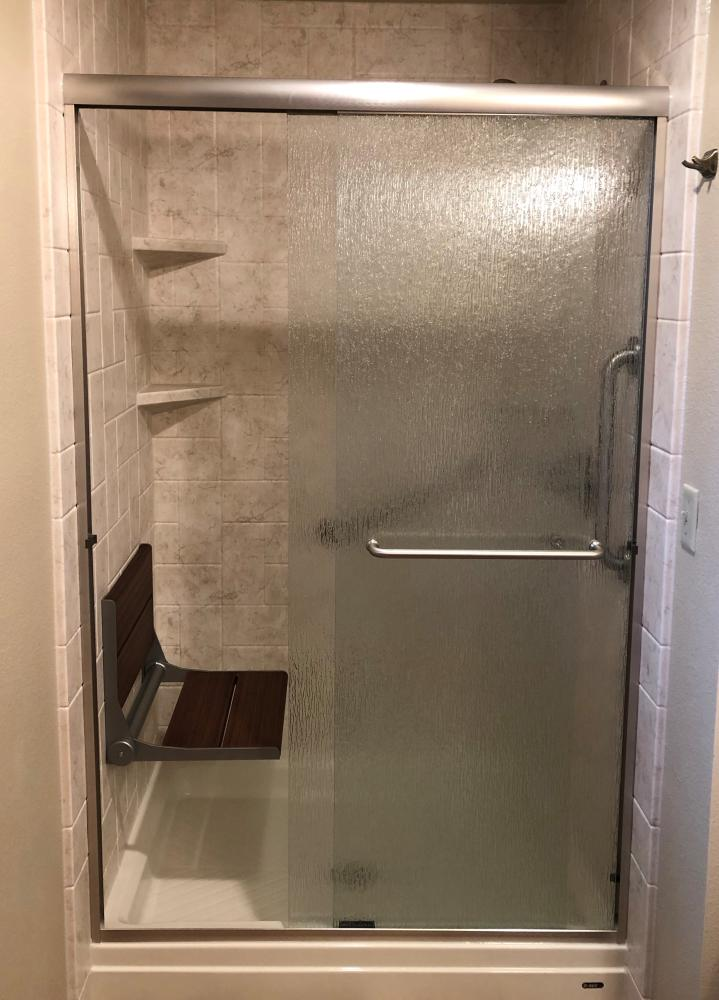 Biscuit shower base with Tivoli Travertine SSP walls. Rain sliding glass door, brushed nickle fixtures, and Invisia Seat.