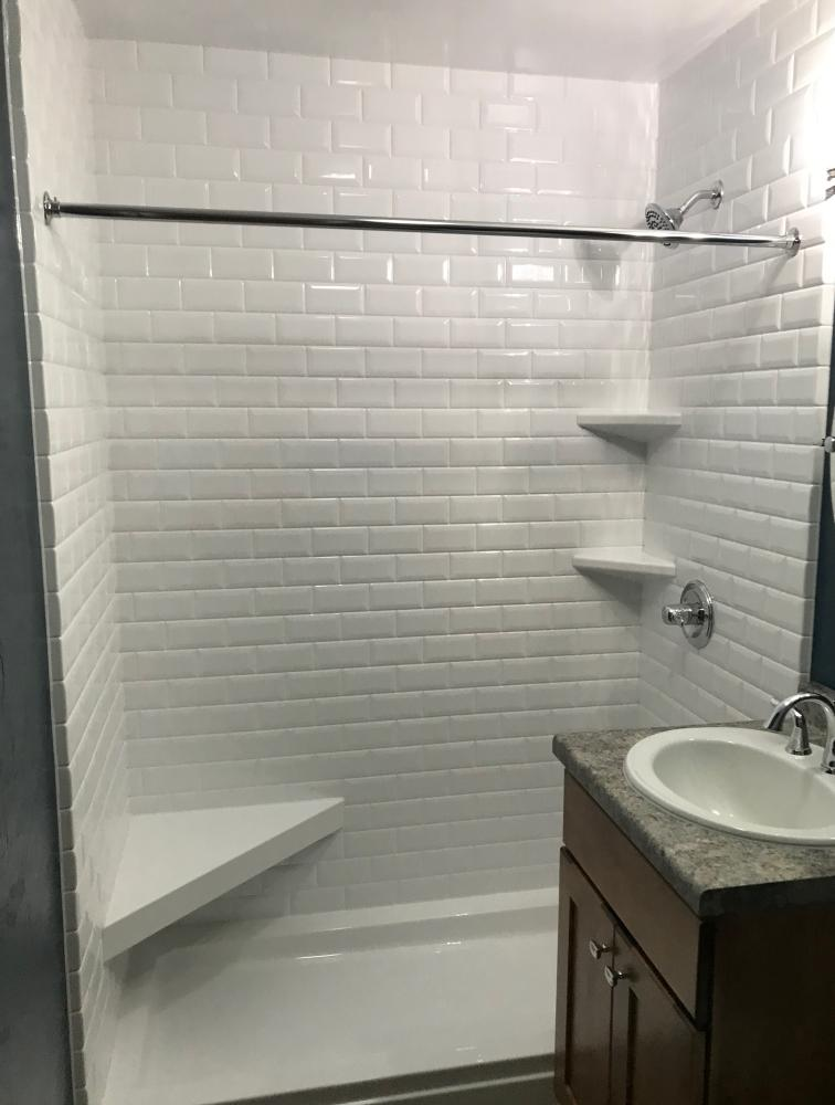 White shower base with white classic subway simulated tile. Corner white seat and corner shelving.