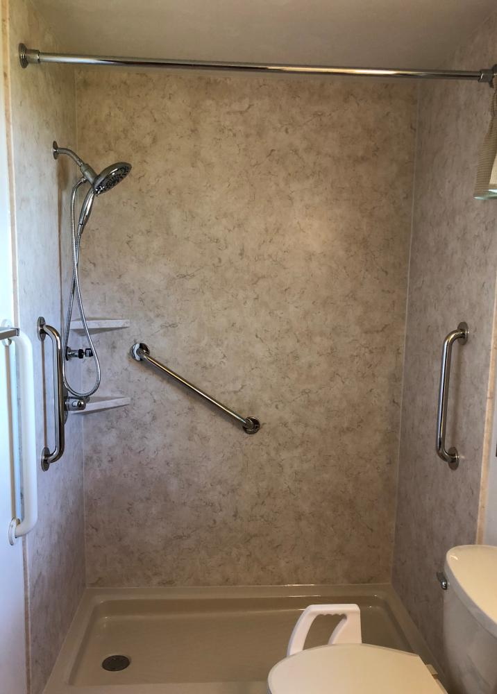 Almond shower base with Tivoli Travertine SSP walls in matte finish. In2ition hand held shower head and chrome safety bars.