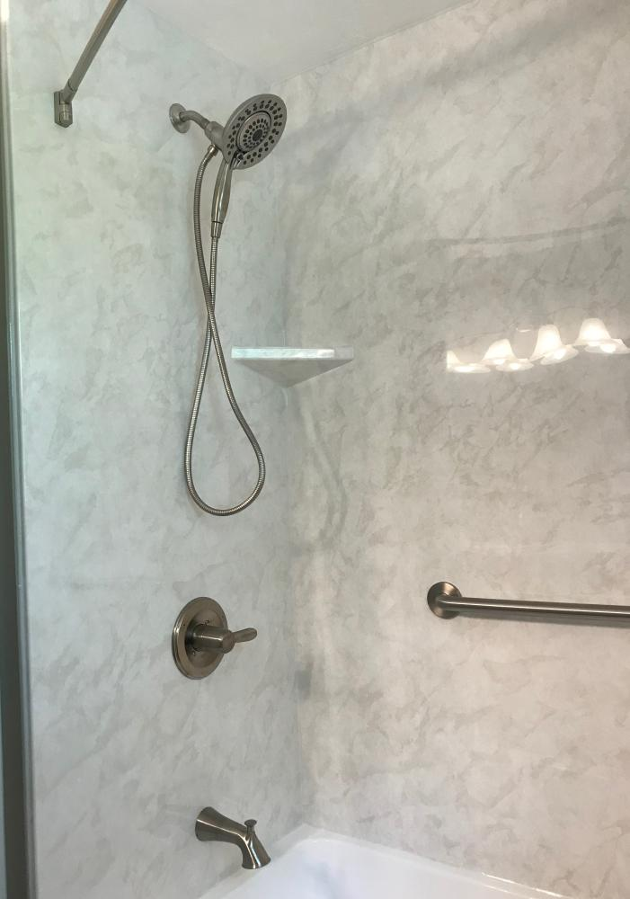 White tub with white marble SSP walls and corner shelf.