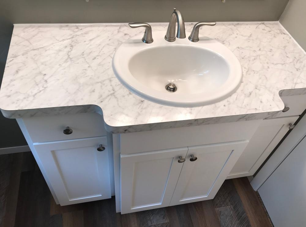 Formica Carrara Bianco with shaker style doors. Oval white sink and stainless steal widespread lavatory faucet.