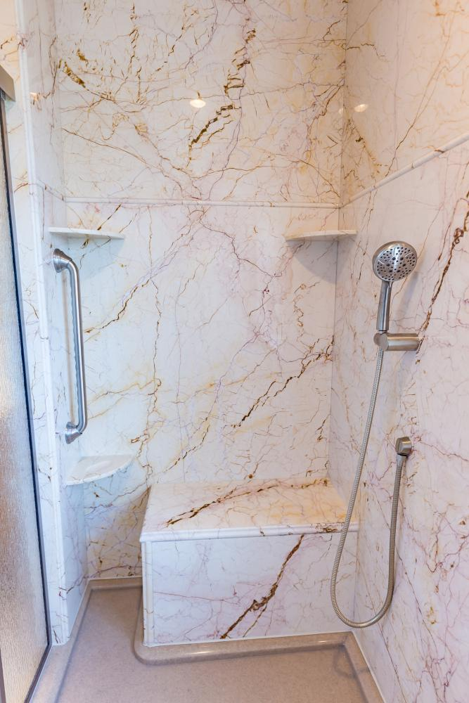 This walk-in shower update included taking away the old tile and replacing the walls with slabs of natural marble in Softel Gold. The renovation also included a custom built bench seat, low profile shower base, swinging shower door, grab bars and handheld shower near the bench seat. Pictured here are brushed nickel Moen accessories, but this lovely marble also looks amazing with oil-rubbed bronze and brushed gold.