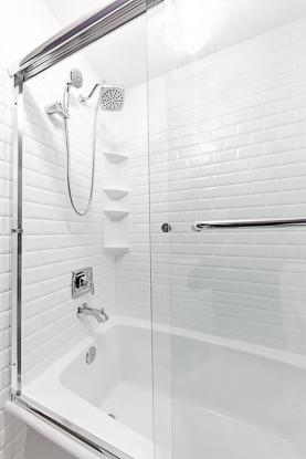 Tub shower combination with chrome fixtures and sliding shower door.