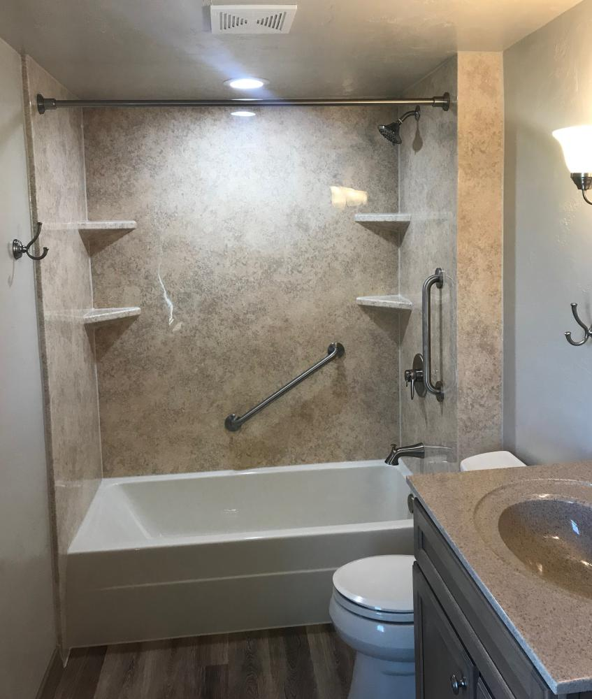 Biscuit tub with Sonoran Granite SSP walls in gloss finish with Sonoran Granite corner shelves sand stainless steal grab bars.