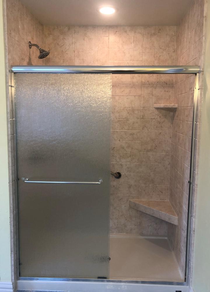 Tivoli Travertine walls, corner seat, and corner shelve in Newport simulated tile.  Rain sliding glass door with chrome.