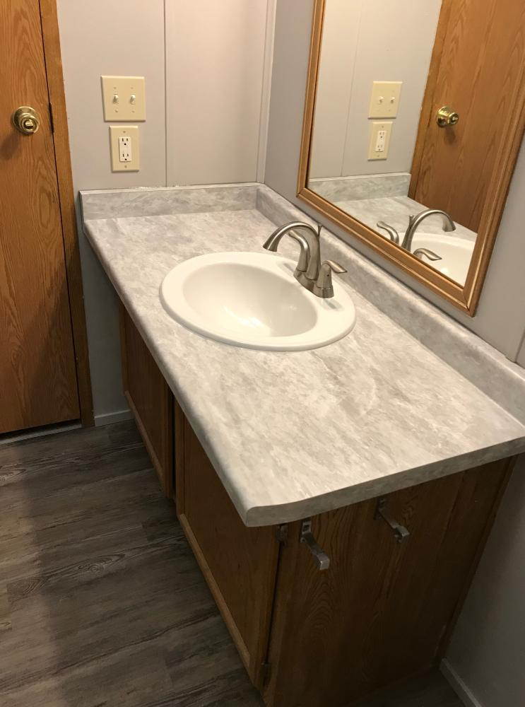 White Bardiglio Formica counter top with white kolher drop in sink.