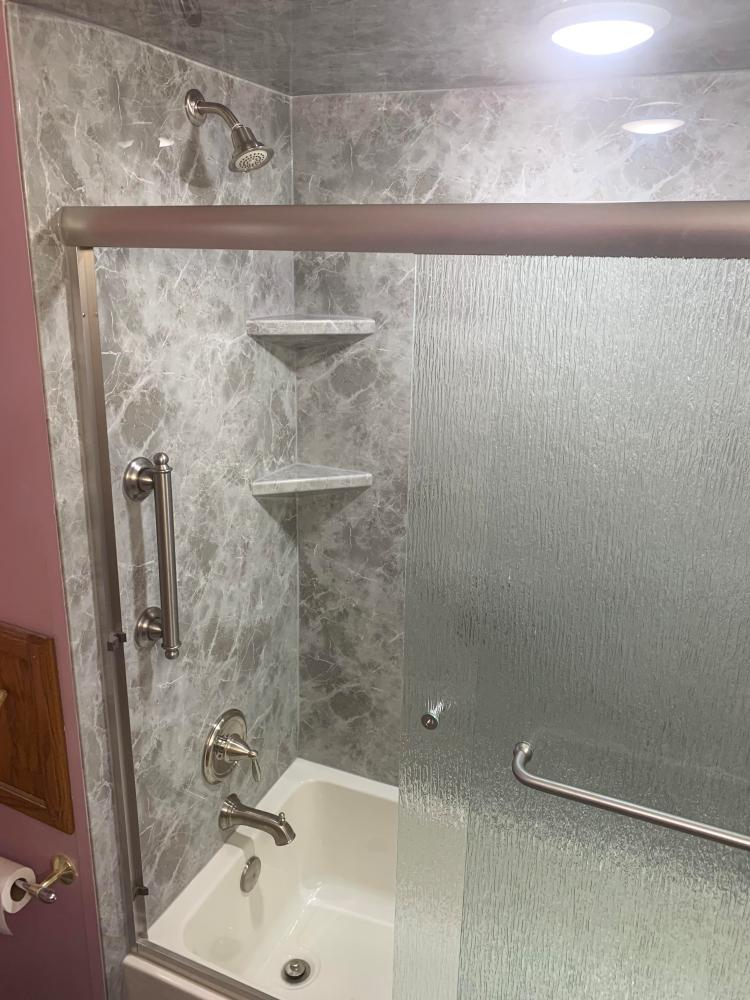 Removed the outdated tub/shower and replaced it with Re-Bath tub and surround along with custom glass doors.