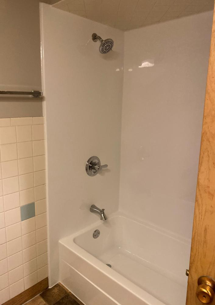 Durabath SSP White wall surround with white base and delta fixtures.