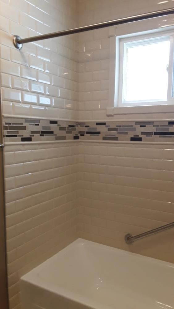 Removed old tub, replaced with new, tore out aging tile and replaced with dura-bath  grout-free subway tile wall surrounds with a mosaic inlay, trimmed window in material, removed shower door, replaced with shower curtain