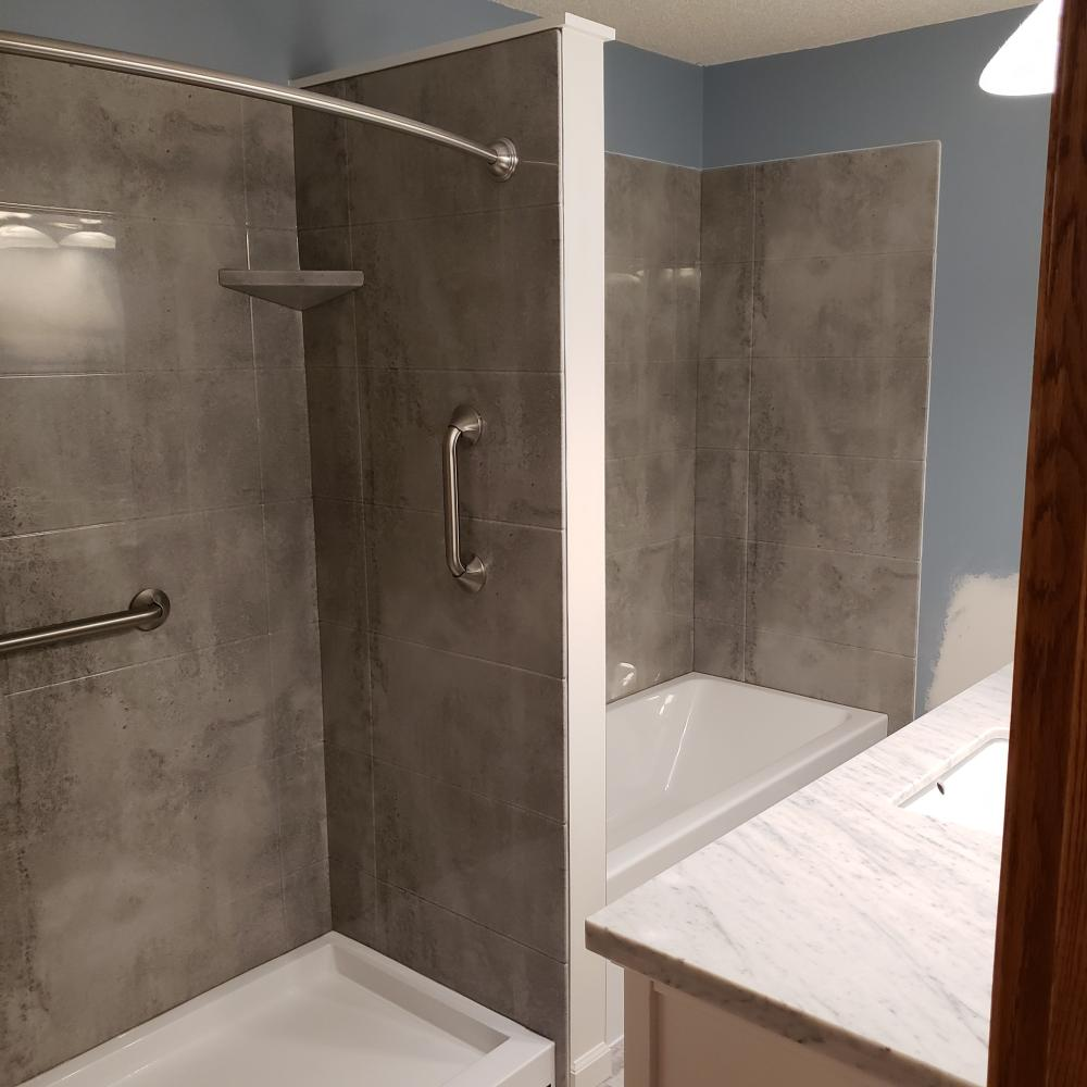 Removed the outdated fiberglass corner shower and installed a walk-in shower. Also, removed the jacuzzi tub and installed a Re-Bath soaking tub. Both have a groutless, non-porous groutless surround, color called Concrete.