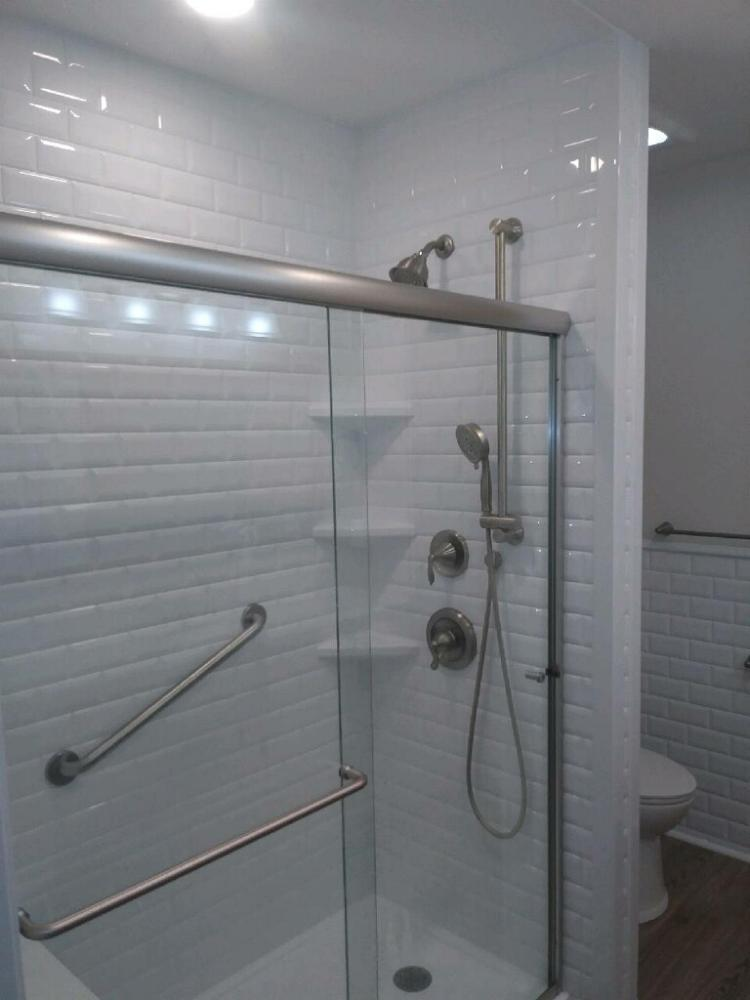 Sleek shower shouts bright and white.  Brushed nickel fixtures complement this modern look.