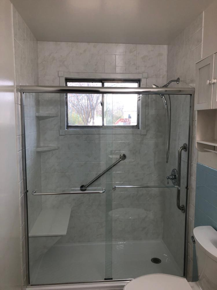 Color of material is white marble in newport print, grab bars, low threshold shower base, with bench seat and shelving